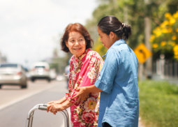 caregiver assisting elder woman in walking