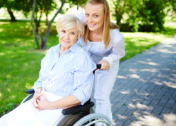 elder woman on wheelchair assisted by caregiver