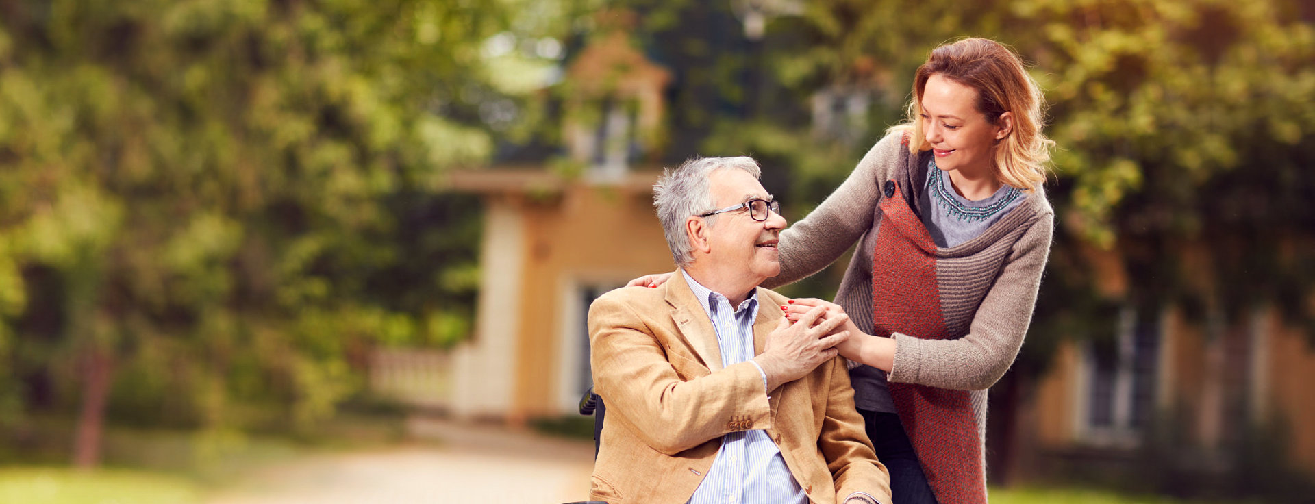elder man on wheelchair and caregiver looking to each other