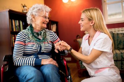 caregiver and elder woman holding hands