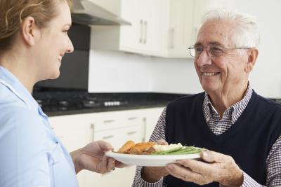 caregiver preparing meal for elder man