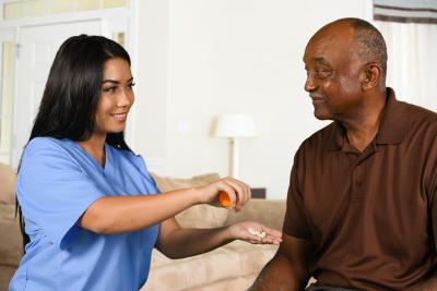 caregiver giving medicine to elder man
